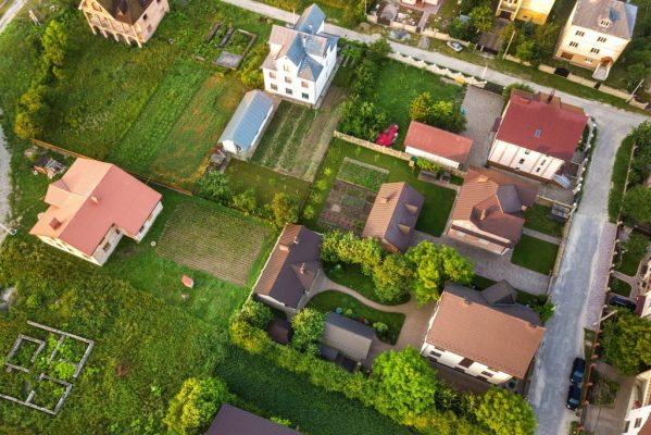 aerial-landscape-small-town-village-with-rows-residential-homes-green-trees-min